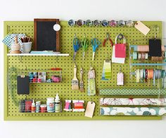 Pegboard is perfect for holding crafts supplies. Cut pegboard to the desired size and frame it with molding pieces found at a hardware store. Paint the entire piece, let dry, and hang it above your workstation. Hooks for pegboards come in various shapes and sizes, so select ones that will easily hold the items you plan to store.