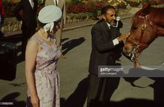 Emperor Haile Selassie patting a horse while Queen Elizabeth II is standing…
