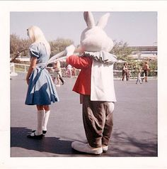 Alice having her apron strings tied (untied?) by the White Rabbit.
