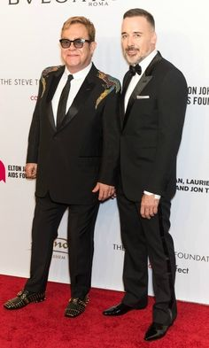 Elton John wore a Gucci jacket and Bulgari jewels as he stood next to his husband David Furnish during his 15th annual AIDS Foundation 'An Enduring Vision' Benefit at Cipriani Wall Street in NYC.