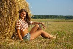 Pretty girl resting on fresh straw bale. Stock Photo - 8996349