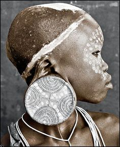 Sure Tribe, Ethiopia. Nale is the daughter of one of the elders of the tribe. The size of the earring disc shows how much the bride price is. The larger the plate in her ear, the higher the bride price.