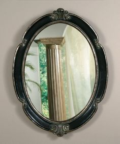Large oval mirror in antiqued black with silver accents, C-scroll motif.