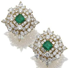 Pair of emerald and diamond ear clips. Each of stylised target design, centring on a step-cut emerald, within surrounds of marquise-shaped, brilliant- and square-cut diamonds, mounted in yellow gold. Sotheby's.