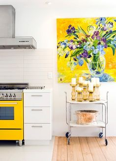I usually don't like super modern design like this, but the yellow stove, funky bar cart, pretty candle arrangement and painting make it feminine. Cute!