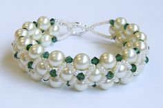 Bead woven bracelet: White 8 mm pearl, emerald crystals, pearl luster seed beads, silver toggle clasp. Right angle weave used.