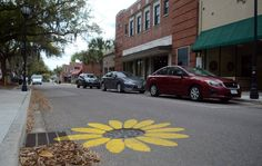 One of the five manholes that were painted by an unknown artist to look like a sunflower along Port Republic Street in Downtown Beaufort as seen on Monday afternoon. (March 2015) - photo from Island Packet; Hilton Head Island, South Carolina  (#1 of 4)