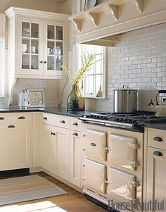 """Spare Aesthetic. In a kitchen designed by Susan Tully, an Aga range works beautifully with the spare aesthetic. The simple black-and-white color scheme adds a nice touch."" (House Beautiful)"