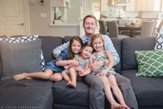 Dad with his three girls, snuggling on the couch. Lifestyle portrait by N. Lalor Photography.