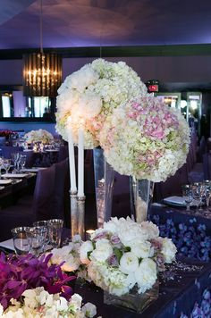 Pomanders of peonies and hydrangeas rest atop tall silver trumpet vases for chic wedding centerpieces.