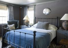 Shades of blue and gray infuse the master bedroom. Linens, Restoration Hardward; blanket, Swans Island; armchair in an Edelman Suede; mirror, Maureen Fullam; curtains in a Fortuny fabric; walls in a Loro Piana fabric.