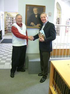 Library Board Chair Mr. Bob Taylor shakes hands with Mr. J. Patrick Boyer, the author of the history of Bracebridge Public Library titled Local Library, Global Passport.  The book was published as part of the Library's Centennial celebrations in 2008.