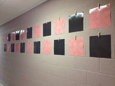 Glue laminated scrapbook paper to wall with a clothespin.  Use that to hang class papers/art/etc on display in hallway.