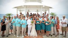 A keepsake photo of the entire wedding party and guests from this gazebo wedding in Cozumel, Mexico. Love the teal bridesmaid dresses and casual groomsmen outfits. | Palace Resorts Weddings ® #destinationwedding