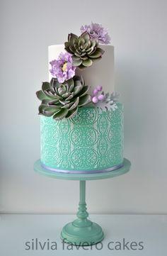 Torta en color menta, lilas y blanco. Dos grandes suculentas y flores silvestres en lila. Sobre stand al tono.| Mint and lilac cake. With suculents, and lilac flowers.