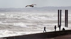 Youths play next to a stormy sea in Brighton