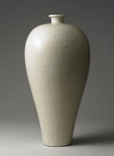Ding stoneware meiping vase. Thrown in three parts, joins discernible at the neck and halfway down the creamy white body. Decorated with carved and incised designs of overlapping petals and a peony scroll. Northern Song Dynasty.