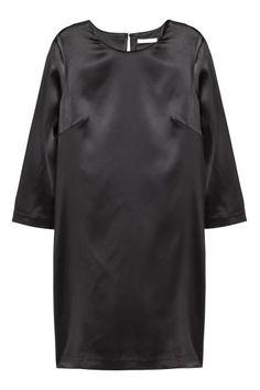 Sukienka z drapowaniem z tyłu: Prosta sukienka z elastycznego błyszczącego materiału. Rękawy 3/4, lekko drapowany tył, na plecach rozcięcie z haftką na karku.