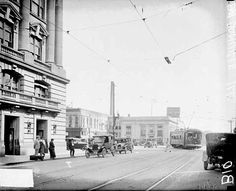Image of a streetcar turning a street corner in a commercial area in Danville, Illinois. Four people are standing on the sidewalk in the foreground, and a woman is crossing the street behind the streetcar. A car in the foreground is driving in the direction of the camera - This photonegative taken by a Chicago Daily News photographer may have been published in the newspaper - 1926.