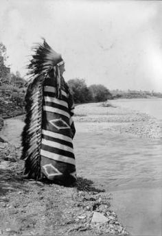 Tom Nash, a (Crow) man, poses on the edge of a river near Sheridan, Wyoming. He wears a blanket and a feather warbonnet headdress. Entitled: The Custer Massacre Sheridan, Wyoming Burlington Route