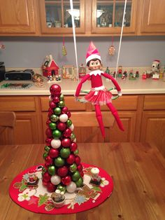 Day 14, 2013 - Sprinkle made a swing from candy canes and it swinging on the light above the kitchen table - Elf on the Shelf Idea - Preschool Christmas Activity