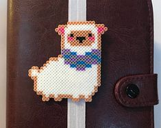 How cute is this llama planner band / bookmark from Happy Hearts Paper Co.?! Check out happyheartspaperco.etsy.com for more fun and unique handmade perler bead planner goodies. They have planner bands, bookmarks, planner clips, page markers, magnets, and more! #planner #planneraddict #plannerlove #plannerspread #plannerlayout #plannerpages #plannercommunity #plannergirl #llamaperlerbeads #llama #bookmark #books #bookworm #perlerbeads #beadwork #etsyseller #etsyshop #etsyfinds
