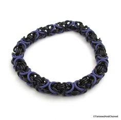 The chainmaille Byzantine weave is a classic, well known weave that has endless possibilities. Here, the main weave is comprised of black anodized aluminum jump rings. The addition of purple rubber O