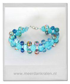 Deze armband is kruislings geregen met speelse blauw getinte kralen (glas en kunststof), in verschillende formaten op blauw staaldraad.