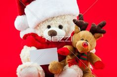 winter copy space - Shot of Christmas themed toys holding a white card on a red background.