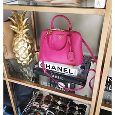 pink prada cross body bag, prada trapezoid pink bag, how to use chanel book as decoration, gold pineapple home decor