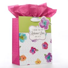 """Medium Gift Bag  Redeemer Lives Range  Floral   Constructed of heavyweight, coated paper. Features white satin ribbon handles, attached gift tag (floral design with """"a flower""""), and an insert sheet of pink tissue paper.   * Heavyweight, Coated Paper  * Size: 20 x 12 x 24.5 cm  * Attached Gift Tag  * Pink Tissue Paper Insert  * Bible Verse - Job 19:25  PRICE: R35 per Bag."""