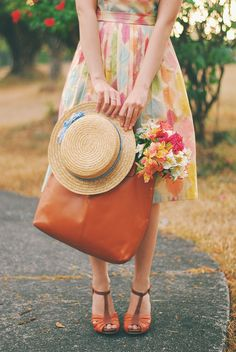 Pastel abstract print dress, straw hat, rust leather tote with flowers, and brown and rust strappy heels