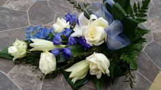 Hand tied funeral spray with lilies, roses and delphiniums.