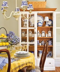 Love the cabinet full of transferware.  This is a very inviting dining area.  I love the blue and white mixed with the yellow.