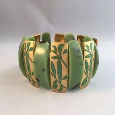 "Acrylic faux jade and enamel filled plant shapes on goldtone links stretch bracelet.  Measures 1.5"" wide.  Pre-owned. Excellent condition.  Free shipping. Ships within 3 business days within the US only via USPS First Class mail."