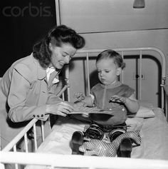 Katherine Hepburn visiting a child in a polio hospital, early 1940s.