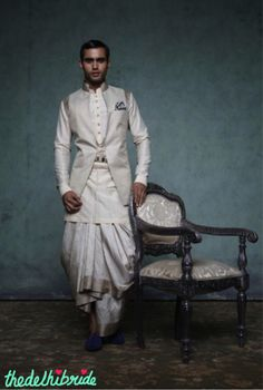 A crème, textured open Nehru jacket with handloom borders, worn with a crème kurti and draped Kanjeevaram sari dhoti. Ensemble enhanced with a pleated kamarbandh fastened by a jewel belt and with intricate zardozi buttons on the kurti. A contrasting pair of blue velvet juttis adds drama to the look.