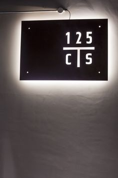 Concrete wall. Polished Plaster.  Metal sign.  Laser cutting detail. 125 Church Street, Designed by Meraki Design Studio