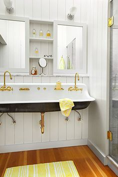 A wall-mounted 5-foot sink by Kohler lends a vintage touch to this master bath. Above it, mirrored door panels flank recessed shelves.