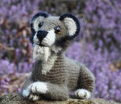 A small handmade crocheted toy (pls don't ask me for the pattern, I just invent them and I already promised often to write them down), approx. 15cm long. A resting smilodon surrounded with early sp...