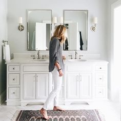 Chic bathroom boasts a light gray single washstand adorned with polished nickel pulls and topped with white quartz placed under a Restoration Hardw…