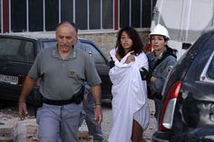 Rescuers-help-a-woman-among-dressed-only-in-a-sheet-after-she-was-saved-from-damaged-buildings-in-Amatrice