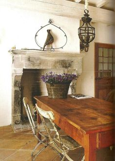 rustic dining room....love that table, pendant light, fireplace, and bird!