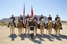 From left, Marine Corps Sgts. Fernando Blancas, Jedidiah Birnie, Terry Barker, Jacob Cummins, Cpls. Nicholas Davis, Alicia Frost and Javier Castellon post with Staff Sgt. Nicholas Beberniss for a mounted color guard portrait with Elephant Mountain in the background at the stables at Marine Corps Logistics Base Barstow, Calif., Aug. 10, 2017. The unit is celebrating its 50th year of service in 2017. Marine Corps photo by Laurie Pearson