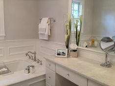 To modernize and soften this master bathroom, the walls are painted in Farrow & Ball Dimpse. Classic moldings add a touch of traditional to the space, while a deep soaker tub features a clean marble surround. Photos and florals from NDI bring a personal touch to the room.