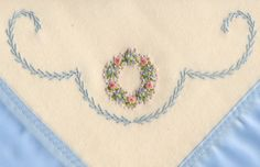 Ivory wool blanket with embroidered wreath and blue featherstitching.  Made by Trudy Horne.