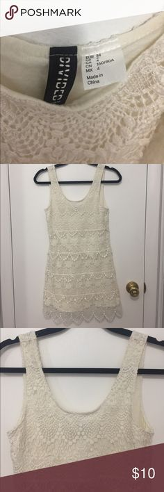 """H&M Divided Cream Crochet Tiered Tunic Tank Dress H&M Divided Cream Crochet Tiered Tunic Tank Dress.  Size 4.  Cute details.  Super short.  It fits perfectly mini and I am 5'2"""".  Shell: 100% Polyester.  Lining: 100% Cotton.  No tears. What I can see hit some wear on the straps.  Machine wash cold, line dry.  From a pet free and smoke free home.  Made in China. Divided Dresses Mini"""