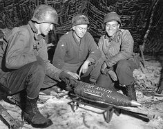 WWII photo of U.S. soldiers sending their New Year's greeting to Adolph Hitler via a 155 mm mortar shell.