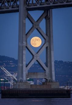Full moon rises above the eastbay hills, framed by the Bay Bridge, by Camera West.