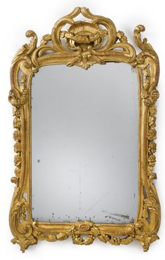 A Louis XV/XVI transitional carved giltwood mirror circa 1765 the frame carved with acanthus and grape clusters and vines, surmounted by a rocaille centered by ribbon-tied leaves.
